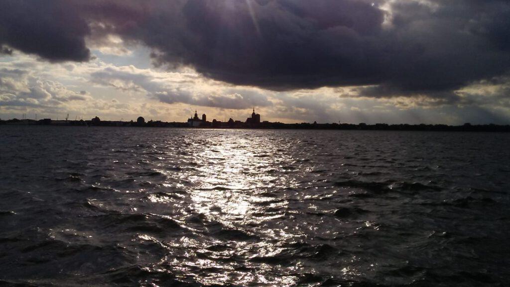 Das Meer und stark bewölkter Himmel. Am Horizont die Skyline von Stralsund.