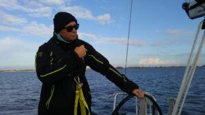 Ein Mann in schwarzer Segelekleidung am Steuer einer Segelyacht. Leicht bewölkter Himmel.