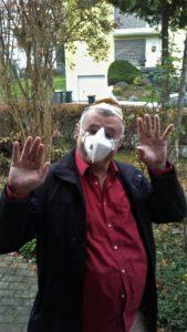Ralf Hafner trägt einen braunen Kaffeefilter als Mütze und eine FP2 Maske als Karnevalsverkleidung.